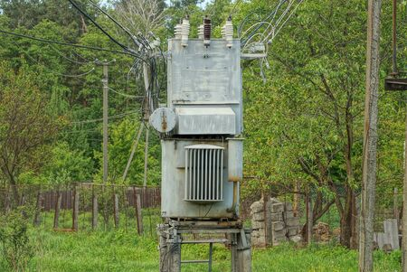 one gray large iron transformer with electrical wires stands on the street against a background of green vegetation