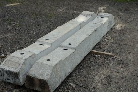 two long concrete gray sleepers for the railway lies on the ground outside