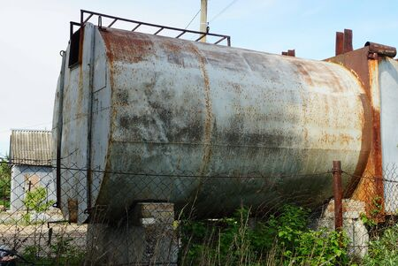 one old iron gray tank in brown rust behind a metal fence on a street