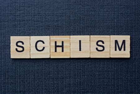 text on word schism from gray wooden letters on a black background