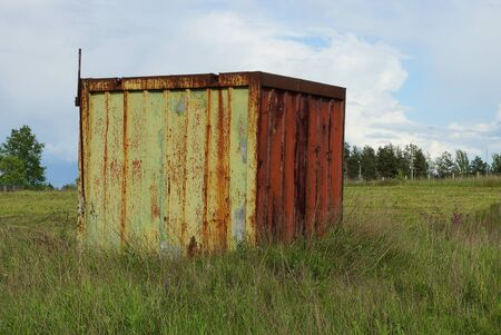 old yellow iron container in red rust stands in green grass