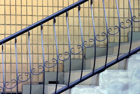 black iron handrails with a forged pattern on the stairs with white concrete steps against a brown wall Standard-Bild