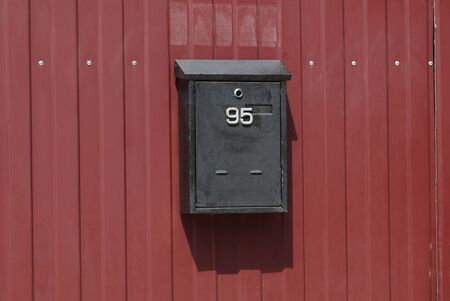 one black iron mail box hanging on a red metal fence wall in the street Standard-Bild