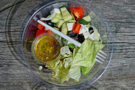 fresh greek salad food in a transparent bowl with sunflower oil and a plastic white fork stands on a gray table Standard-Bild