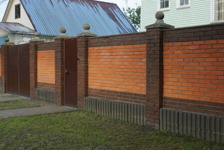 brown and red brick fence wall with a closed metal door on the street Standard-Bild