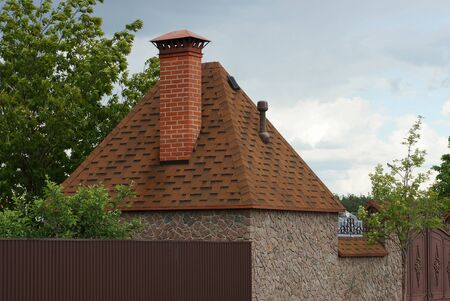 private stone house with a brown tiled roof with a red brick chimney against a gray sky