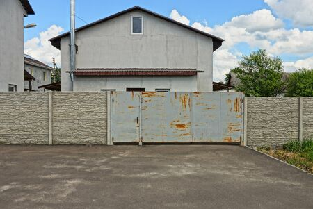 gray metal gate and concrete fence on the pavement in front of a private house with a window against the sky and clouds Standard-Bild