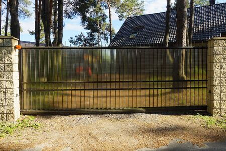 large black closed metal gates and part of a gray stone fence on the street Standard-Bild