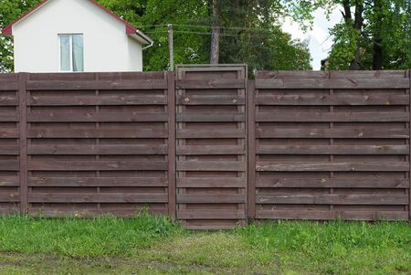 brown wooden fence wall and closed door on the street in green grass Standard-Bild