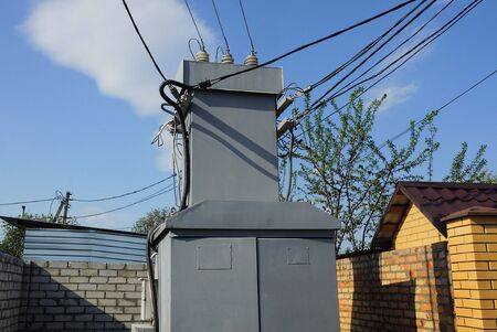 gray iron transformer with black electrical wires stands on the street near a brown brick wall against a blue sky