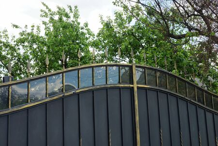 black sharp iron bars on a metal gate and a wall on the street against a background of green branches and sky