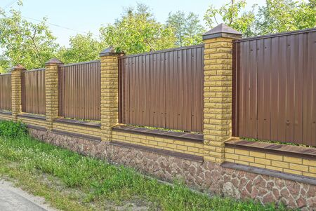 brown wall of a fence of metal and bricks on the street in green grass