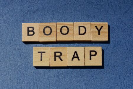 text on gray phrase boody trap in small wooden letters with black font on a blue background