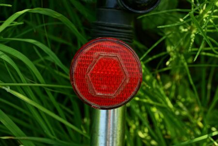 one red round plastic reflector on a gray metal bike pipe in green grass