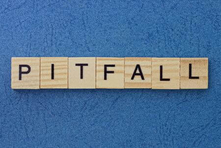 text on gray word pitfall in small wooden letters with black font on a blue background