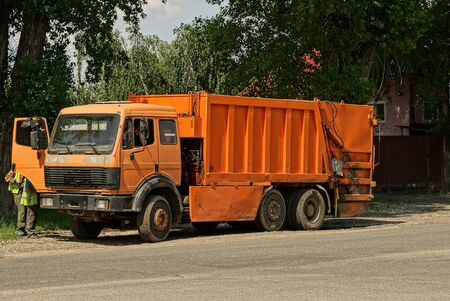 one large orange truck a garbage collector stands on an asphalt road in the street