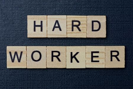 phrase on hard worker from gray wooden letters on a black background