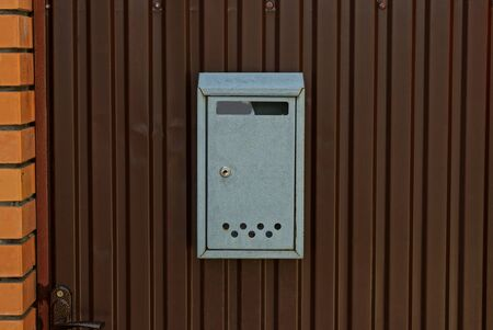 one gray iron mailbox hanging on a brown metal fence wall Banco de Imagens