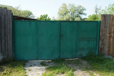 old closed iron gate and part of a gray wooden fence on a rural street in green grass