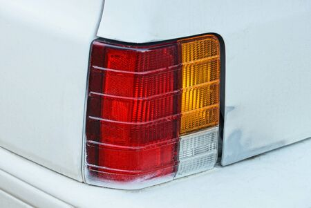 one red large glass taillight on a white metal car