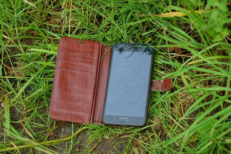 one black smartphone in an open brown leather case lies on the green grass and vegetation in the park
