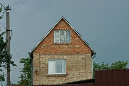 facade of a brown brick rural house with windows on the street against a gray sky Reklamní fotografie