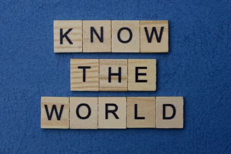 phrase know the world in small square wooden letters with black font on a blue background Standard-Bild
