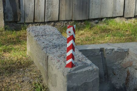 one striped iron pole limiter with a reflector on a gray concrete block on the street by the road