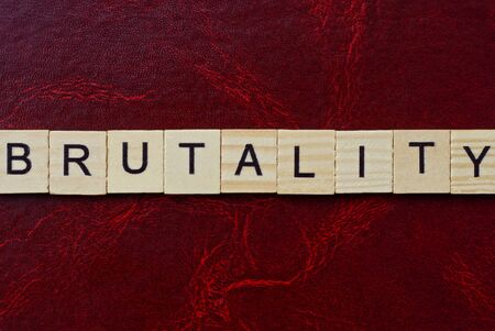 text the word brutality from gray wooden small letters with black font on an red table