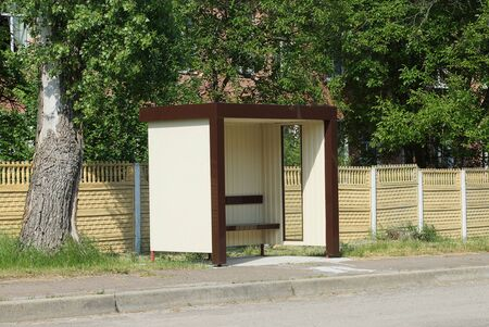 one empty brown plastic bus stop outside on the road in front of a yellow fence Standard-Bild