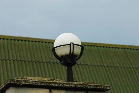 one white round lantern on a fence in the street against a green roof and blue sky