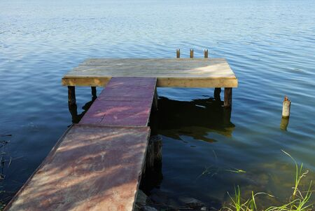 brown long bridge of wooden planks on the lake water near the shore