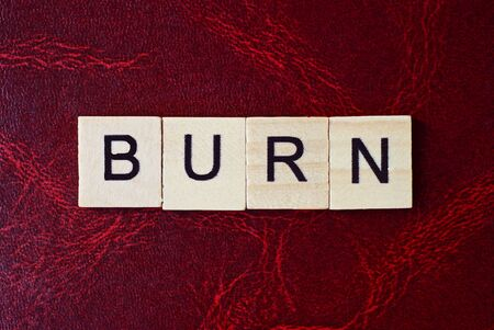 text the word burn from gray wooden small letters with black font on an red table