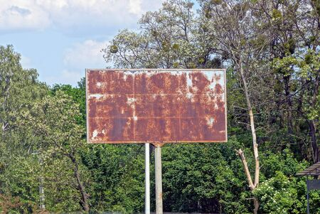 one old iron billboard in brown rust on the street against a background of green trees and sky Standard-Bild