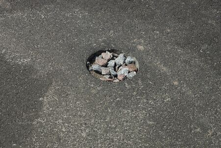one round pothole pit on the gray asphalt of the road