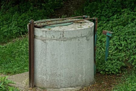 one old gray closed concrete well stands on the street in green vegetation Standard-Bild