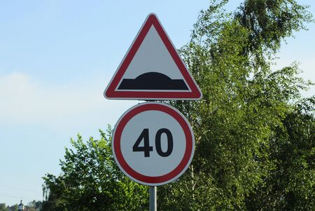 two road signs speed limit and speed bump on an iron pole against a green tree and blue sky Standard-Bild