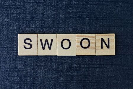 text on word swoon from gray wooden letters on a black background