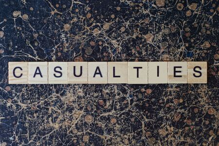 word casualties from wooden letters in black font on a brown shabby wall with a pattern