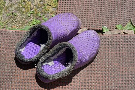 two old lilac plastic slippers stand on a brown doorstep in the street