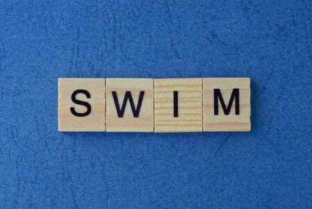 text on gray word swim in small wooden letters with black font on a blue background