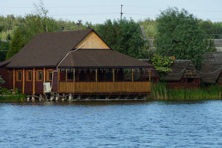 one large wooden brown house with an open veranda over the lake water on a background of green vegetation
