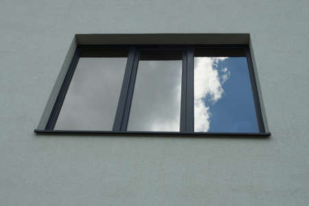 one black square large window on the gray concrete wall of the building Standard-Bild