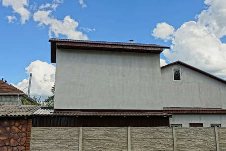 gray concrete attic of a rural private house behind a fence against a blue sky and clouds