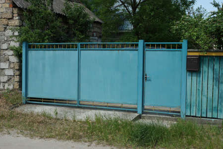blue rural iron gate and part of the fence in the street Standard-Bild
