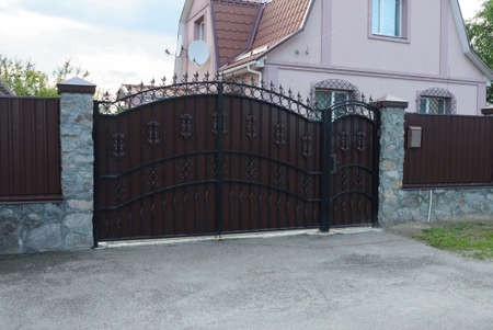 a large brown iron gate with a black forged pattern and part of a gray stone fence on the street Standard-Bild