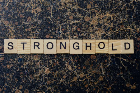 word stronghold from wooden letters in black font on a brown shabby wall with a pattern