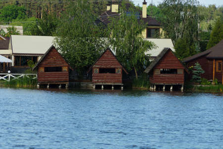 a row of three brown wooden arbors stand on the lake water in green vegetation Standard-Bild