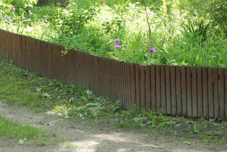 small brown wooden decorative fence outdoors in green grass