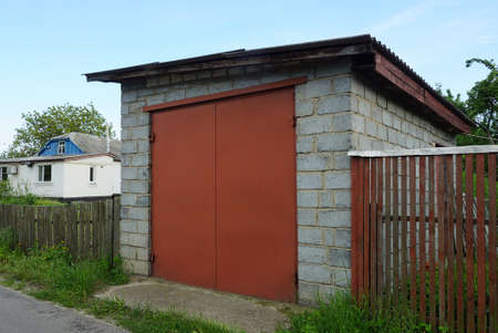 facade of a gray brick garage with red iron closed gates and a wooden fence on a rural street Standard-Bild